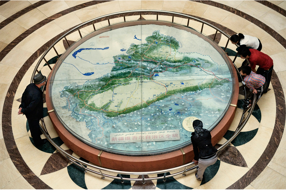 Han and Uighur visitors to the Xinjiang Uyghur Autonomous Region Museum look at a map of Xinjiang, in 2008. The Western Chinese province is home to close to a dozen ethnic groups. Combined, the Uighur and Han populations account for more than 80% of the total population, though the Uighur portion of the population shrinks as more Han migrants flood the province.