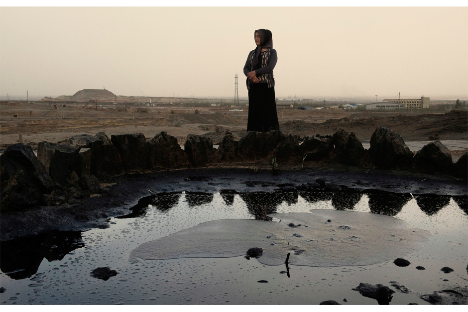 A Uighur woman stands by a pool of oil that has bubbled to the surface in April 2009, near Karamay, a center of energy exploitation in this region. Twenty percent of China's oil production comes from Xinjiang, making it a strategic region for China. The oil and petrochemical sectors account for as much as 70% of Xinjiang's local economy. Locals complain that energy sector profits go directly to Beijing and do not benefit the region.
