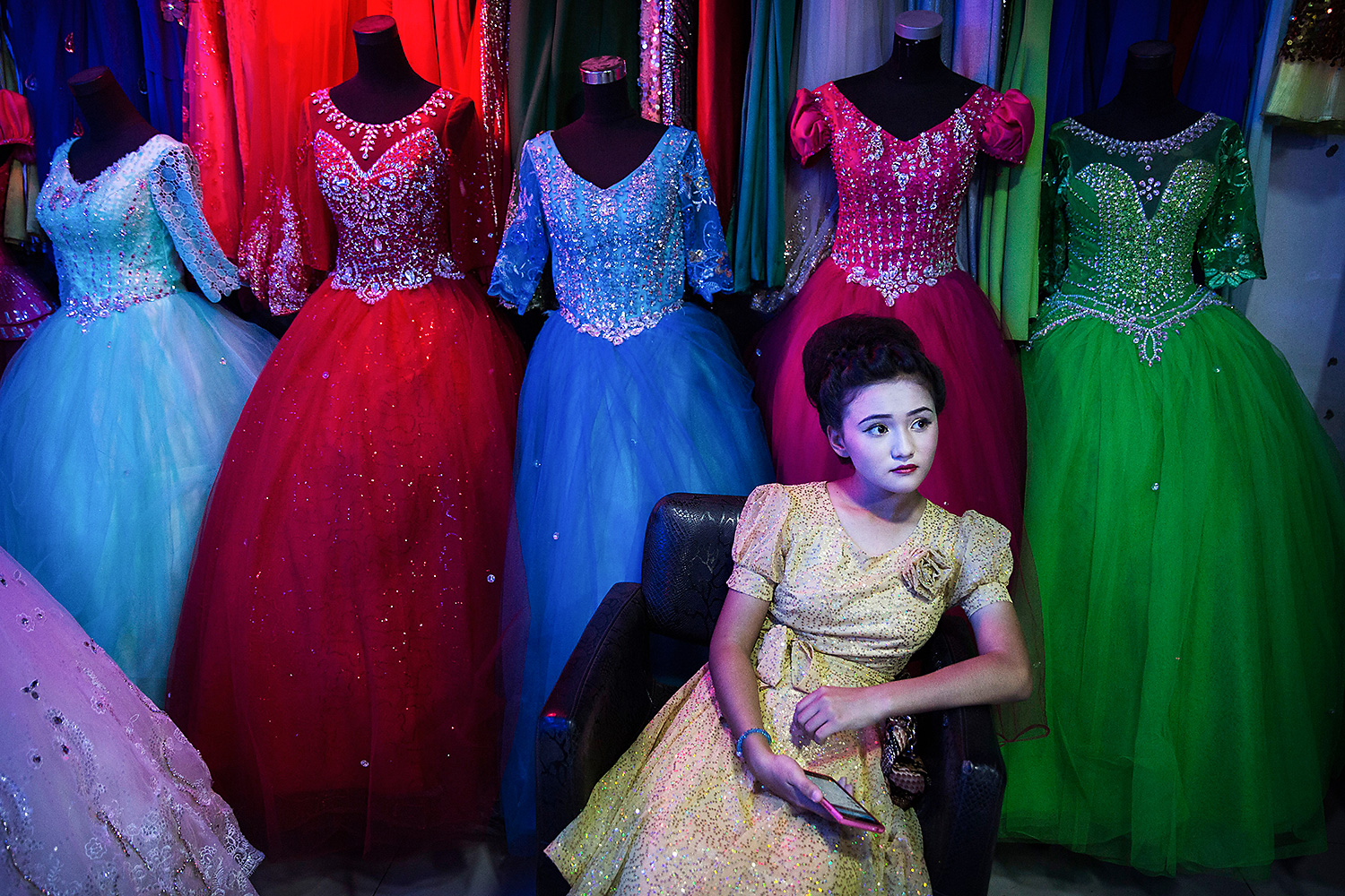 "An ethnic Uighur girl waits in a beauty salon to have her hair done before the Corban festival known elsewhere as Eid al-Adha, or ""feast of the sacrifice,"" in Turpan County, Xinjiang. Though Islam is one of five ""officially recognized"" religions in China, local officials often severely restrict Uighurs' ability to practice their faith. These restrictions, as well as ethnic tensions, have fueled violence in Xinjiang and across China—violence that Beijing uses to justify further repression. Photo by Kevin Frayer @kevinfrayer"