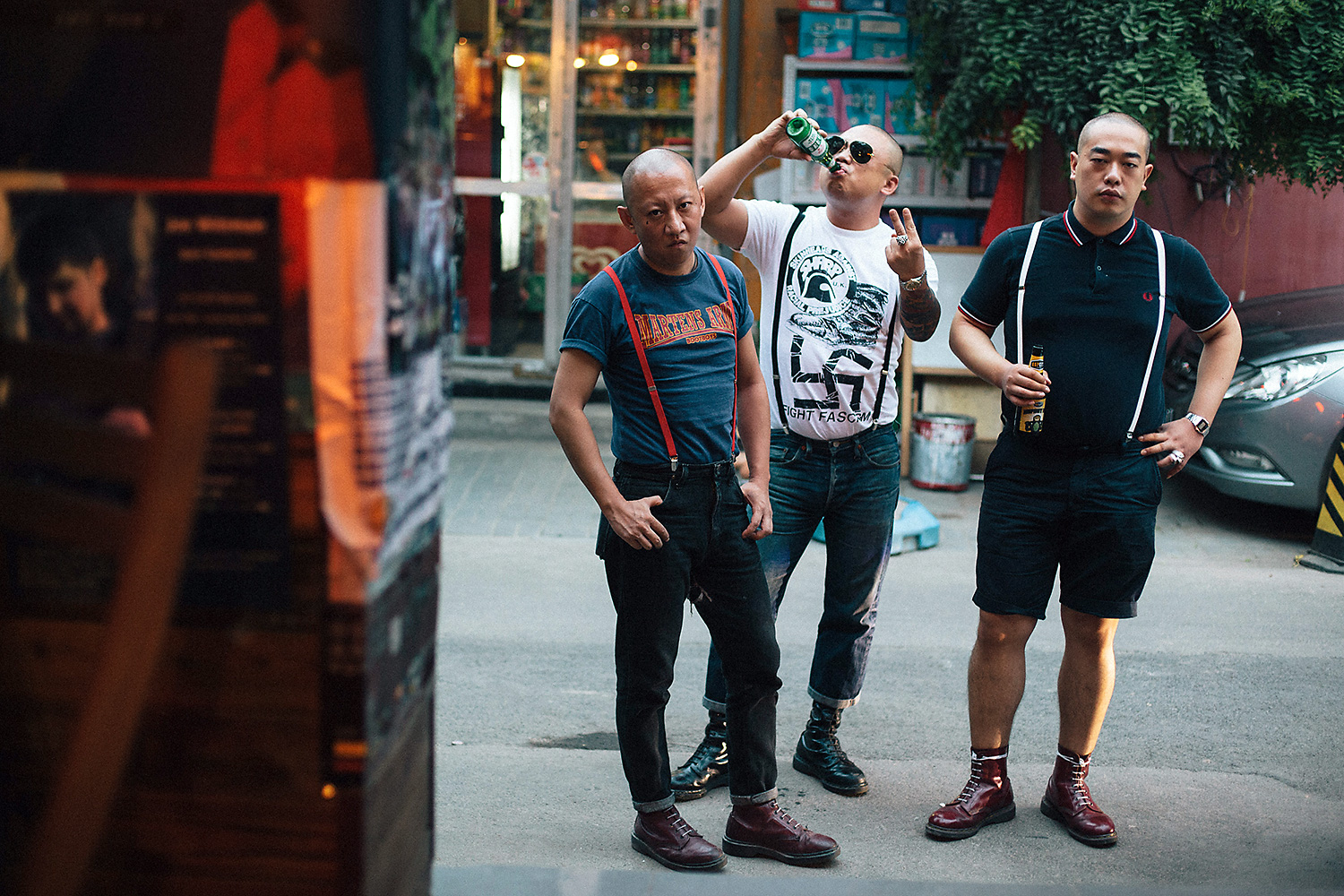 Ma Ke a.k.a. 'Mr. Ma,' Yan Lei a.k.a. 'Bangbang,' and 'TM©' pose on a Beijing street for a portrait. (TM© asked not to reveal his real name.) Bangbang flashes a 'V' in defiance while wearing a t-shirt from the anti-fascist punk movement Skinheads Against Racial Prejudice (SHARP), that depicts a punk-rock favorite Dr. Martens boot stomping a Nazi swastika.