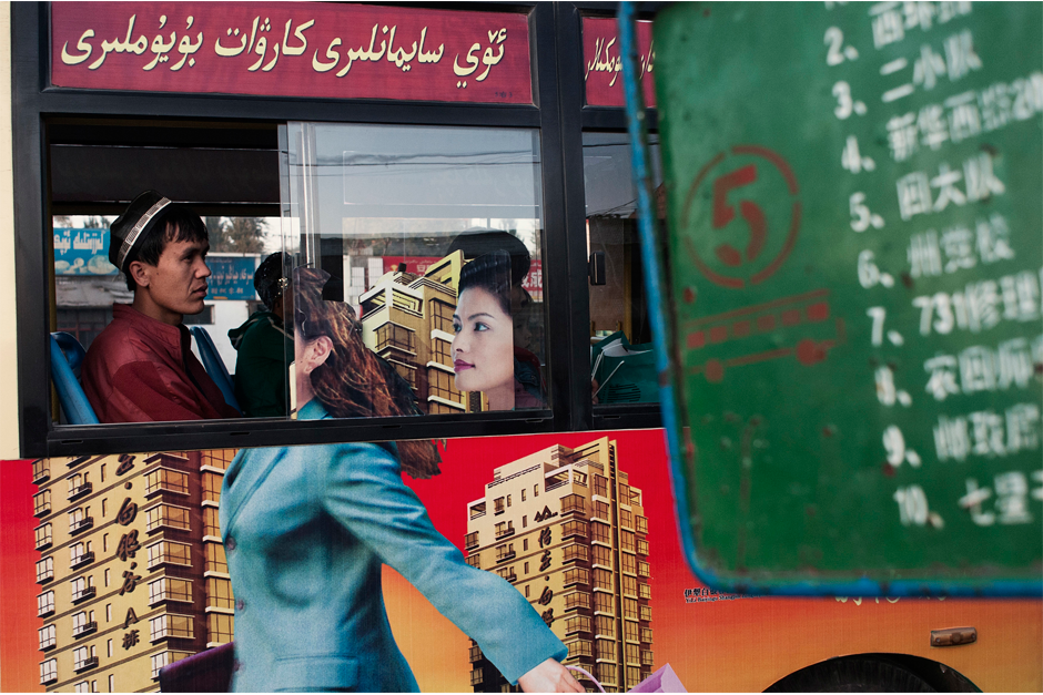 In the county seat of Yiling, a Uighur passenger rides a bus carrying an advertisement for a real estate project featuring a Han businesswoman.