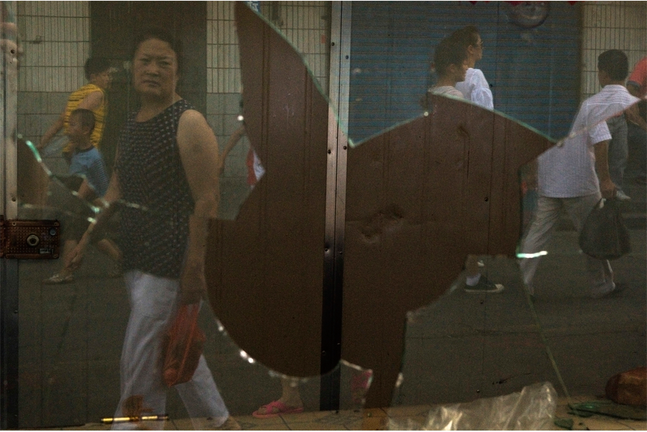 Reflections of passers-by form a fractured view of city life in Urumqi in the shattered window of a small store vandalized during the 2009 riots.