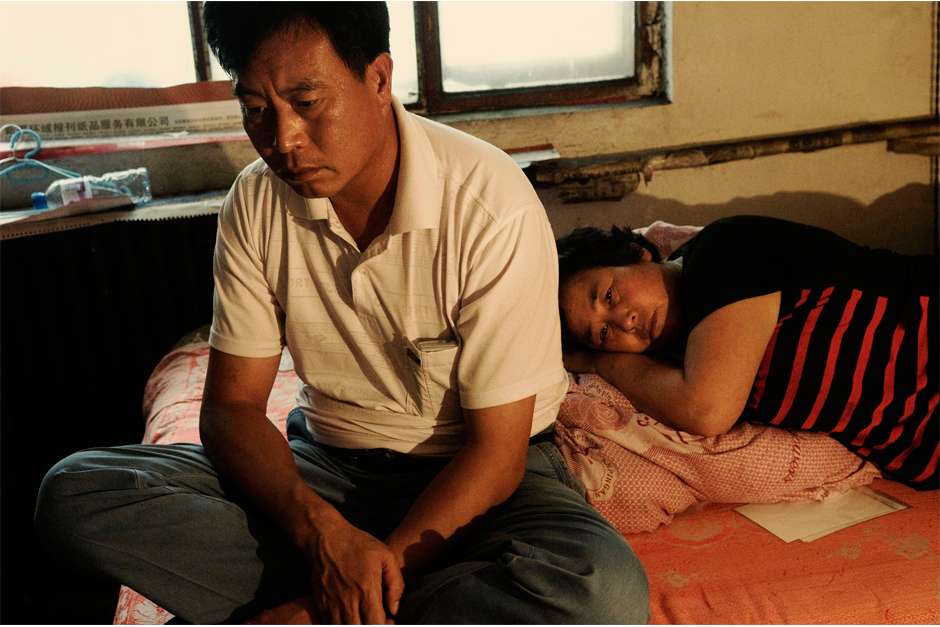 Lu Sifeng and his wife, Zhang Aiying, sit on their bed lost in thought after learning that their son, 25-year-old Lu Huakua, has died from injuries sustained during an attack by a Uighur mob, during the July 5, 2009 riots in Urumqi. The couple, originally from Henan, had moved to Xinjiang a couple of years earlier and found work selling fruit and vegetables.