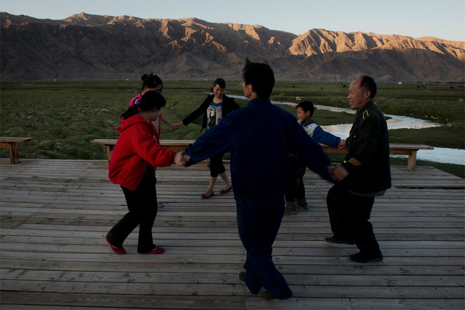 Han migrant workers from Henan dance in the grassland of Tashgurkan at the end of the day in the summer of 2013. Massive investment in the development of Xinjiang has resulted in an influx of Han workers, but, many locals say, has not benefited the local population.