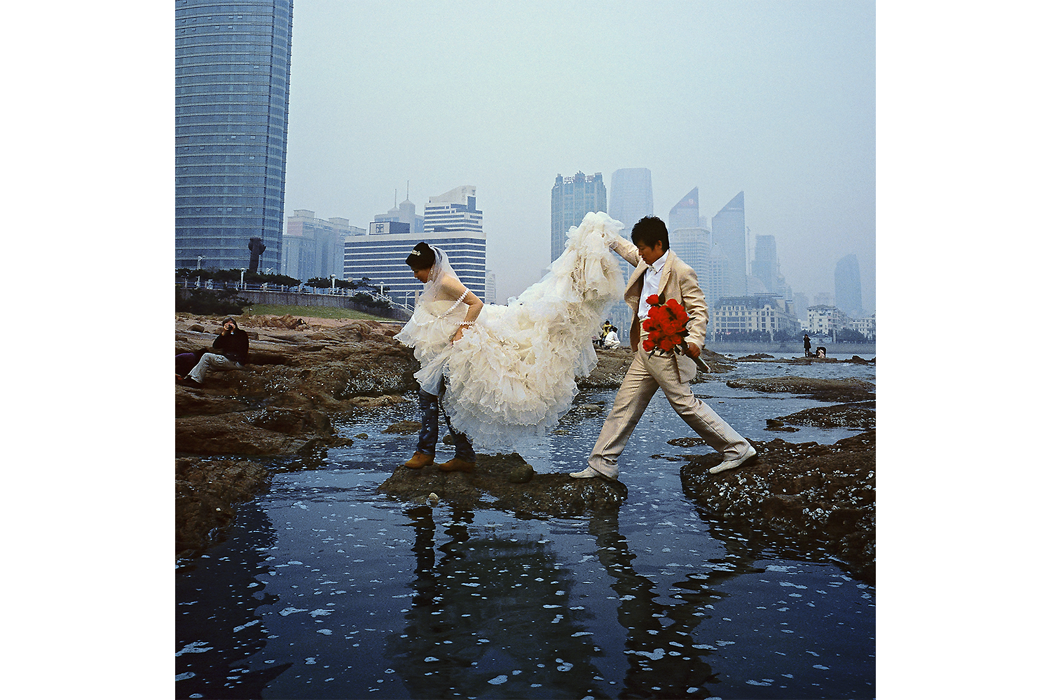 A couple dressed in wedding clothes tries to stay dry after a phots session in Qingdao. Photo by Chris Cherry @christophcherry
