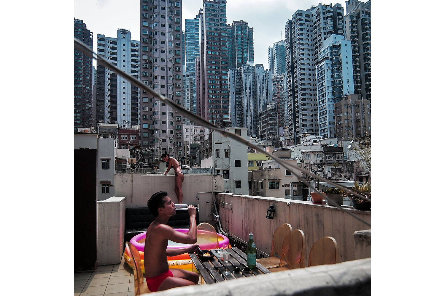 Modern apartment buildings rise in the background, as a couple soaks in the sun on the roof of one of Hong Kong's old buildings in the city's business district. Housing stock remains a problem in Hong Kong, where a large population lives in cramped quarters and the city's real estate remains among the most expensive in the world. Photo by Billy H.C. Kwok @billyhckwok