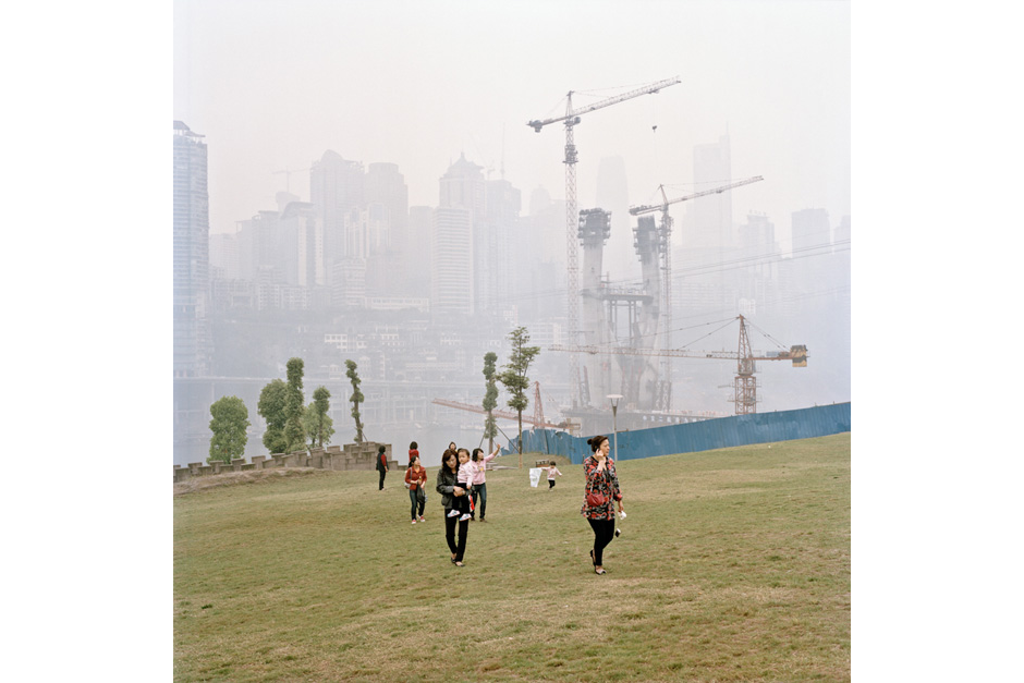 Construction cranes rise in the background mist as women walk with their children across the new grass of a development in Jiangbei. The city's central business district is in the background.
