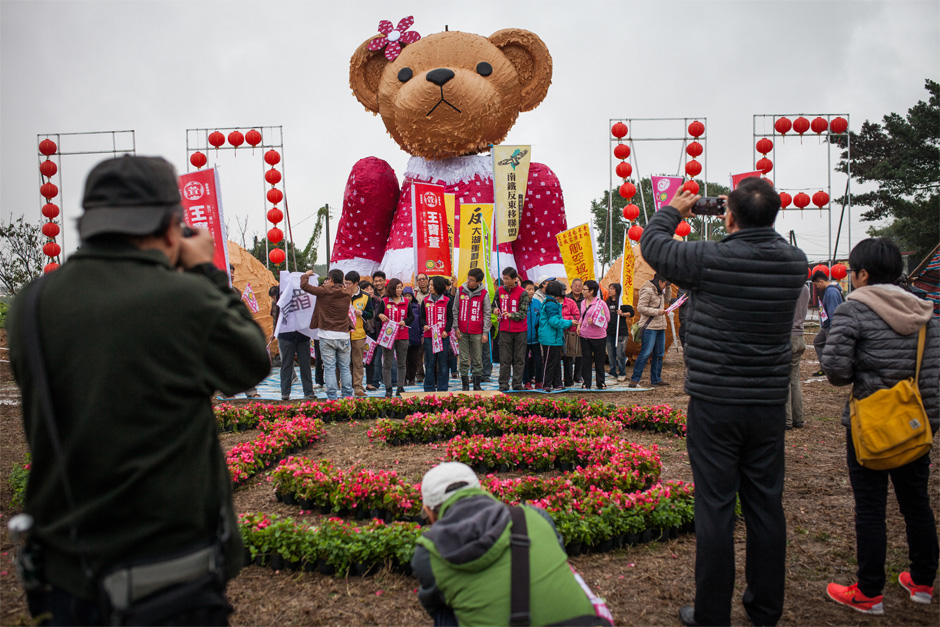 "Wang Bao-xuan, the candidate representing the union of the Green Party and the Social Democratic Party, gathers with supporters around a teddy bear called ""Nüyingxiong,"" a mascot for a protest against an expansion of Taoyuan International Airport that would displace 40,000 farmers."