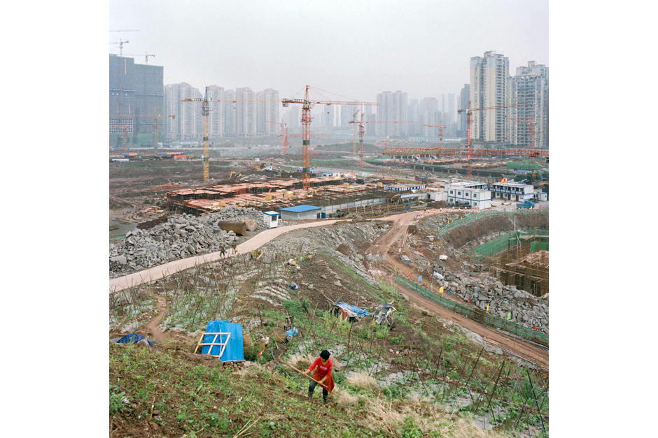 In the Jiangbei district, a woman cultivates a slope as giant cranes rise above a construction site for new housing and temporary structures used by the developers. With the influx of residents relocated from areas affected by the Three Gorges Dam, the Chongqing government began investing heavily in this part of the city, creating a new economic zone.