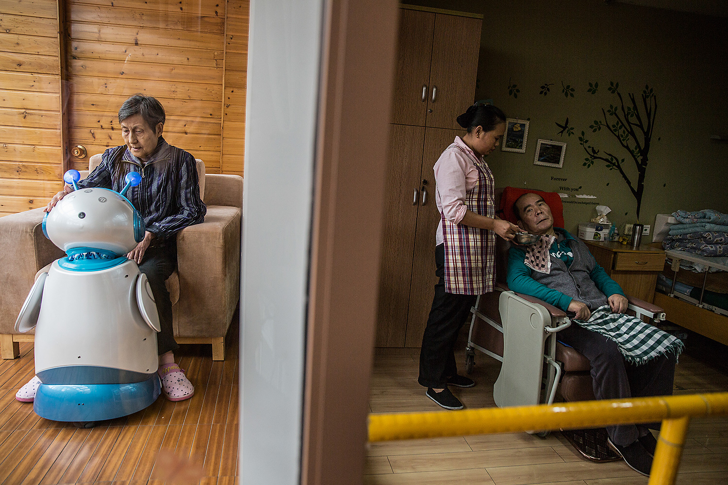 Zhao Qiuying, left, sits with an elder-care robot called Ah Tie, while a staff caregiver looks after an elderly man in an adjacent bedroom at the Hangzhou Social Welfare Center, Zhejiang province. Photo by Chen Ronghui @chenronghui1989