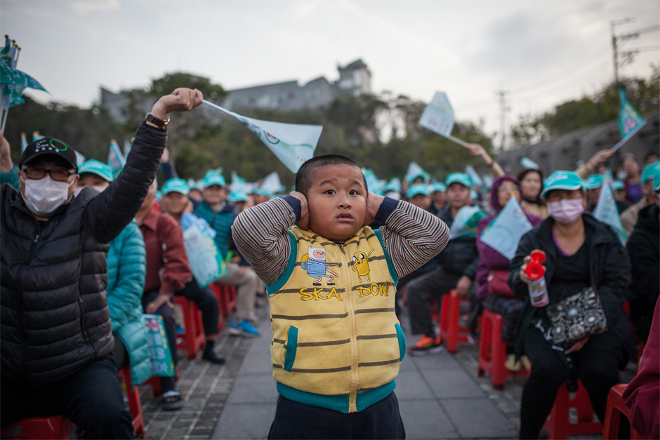 A boy shields his ears from the noise of the crowd at a DPP rally for presidential candidate Tsai Ying-wen in the Shalu district of Taichung.