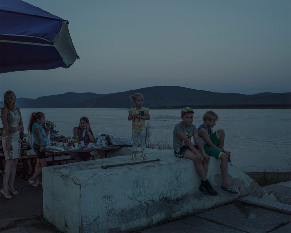 A Russian family sits at a riverside café in Komsomolsk-on-Amur at dusk. The town was largely built using volunteer labor from the Communist youth organization Komsomol, hence its name. Construction of the town was aided by the use of slave labor from nearby prison camps.