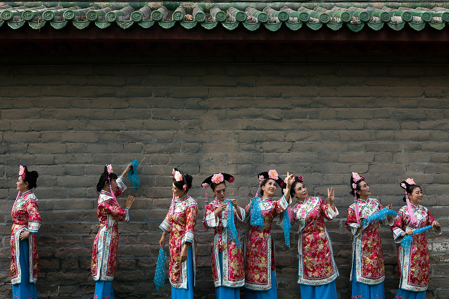Women wearing traditional dresses stand in front of a traditional building at Ditan Park, Beijing on the summer solstice. Photo by Giulia Marchi @giuliamarchiphoto
