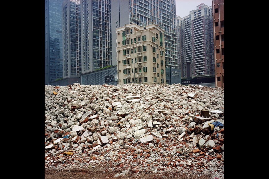 One of the last buildings standing among a pile of debris in Gangxia West Village, Shenzhen, August 2009. The building's owner had yet to sign an agreement with the property developer and the government, preventing them from tearing down the structure and constructing something else on the land. At the time this photograph was taken, part of the building was still being rented out and lived in by migrant workers. Later a local newspaper reported that the building owners were well compensated, some receiving more than US$2 million.