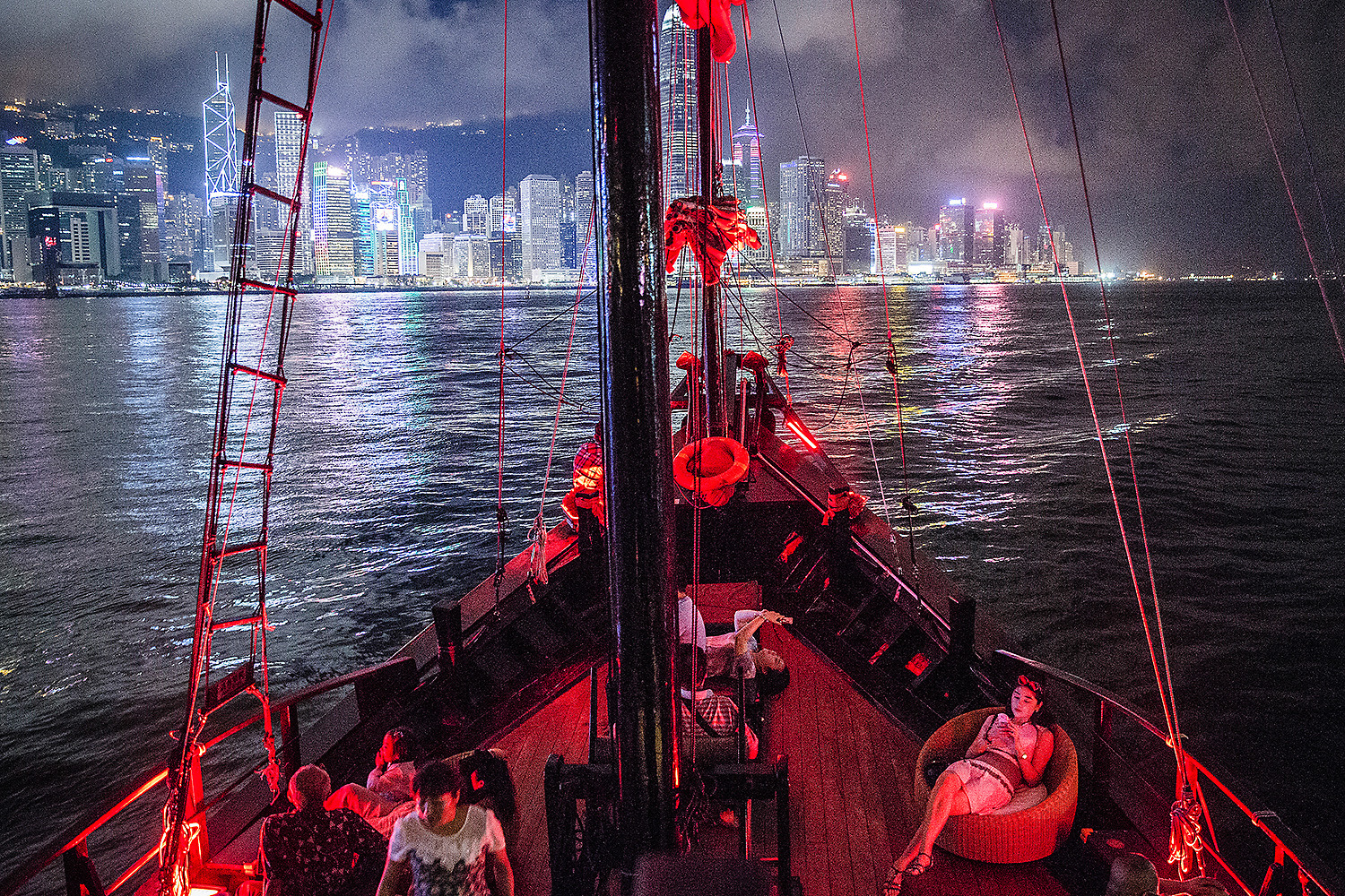 A group of visitors on a Chinese junk boat tour Victoria Harbour in Hong Kong. Photo by Laurence Tan @findlaurence