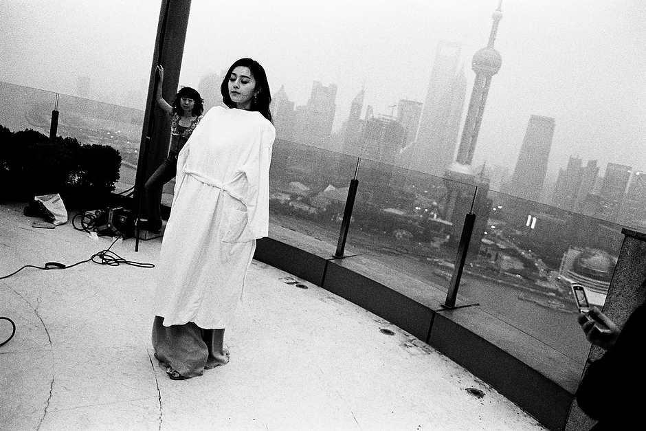 The starlet stands stoic, wrapped in a hotel robe during a rooftop photo shoot set against the foggy late April Pudong skyline in Shanghai.