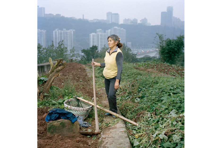 Gan Guoying, fifty-seven, a former rural <em>hukou</em> resident from Chongqing, received her urban <em>hukou</em> (residence permit) in 2006 when she renounced her 500-square-meters of land. She continues to farm here, by the side of a highway bridge, to provide for her family and to sell in the market, earning her between RMB 1,000 and 2,000 (U.S.$160-$320) for her labor. Gan says she feels the city is growing too fast for the people to adapt.
