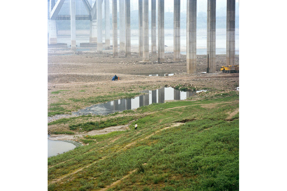 A man walks along the seasonally dry riverbed of the Yangtze, underneath bridge supports that carry traffic high above in Chongqing's downtown. Farmers share these spaces with fisherman, construction vehicles, and recreation seekers.