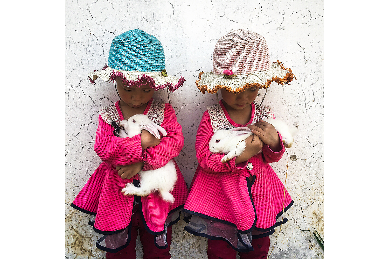 Three-year-old twin sisters Xinran and Xinyi play with their pet rabbits outside their home in Taizicheng Village, Hebei province. Photo by Yan Cong @yancongphoto