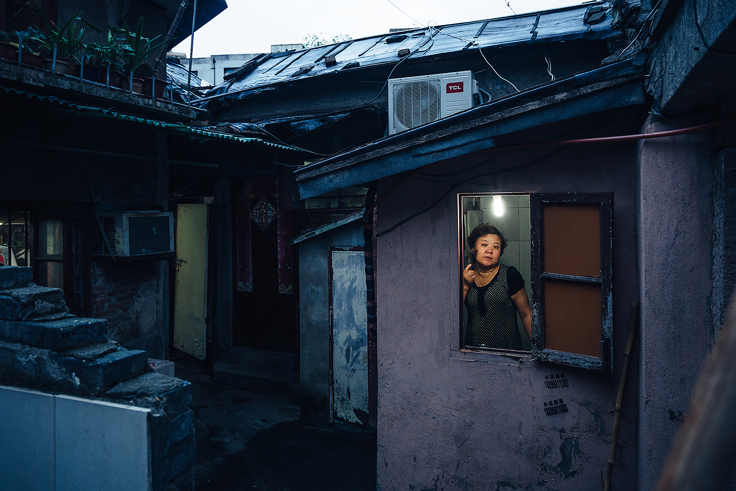 Zheng Ruizhen combs her hair after taking a shower in her Shanghai home. She was one of the last holdouts in her neighborhood, until her husband finally signed away their home after local officials threatened to tear down the bathroom. The couple didn't know how much compensation the Shanghai government was going to offer. Photo by Yuyang Liu @yuyang_liu_