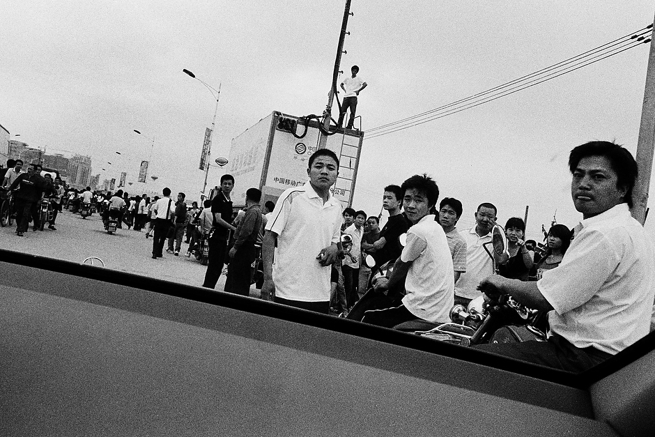 A road crowded with curious onlookers slows the pace of Bingbing's motorcade as it makes its way through the streets of a Shenzhen suburb.