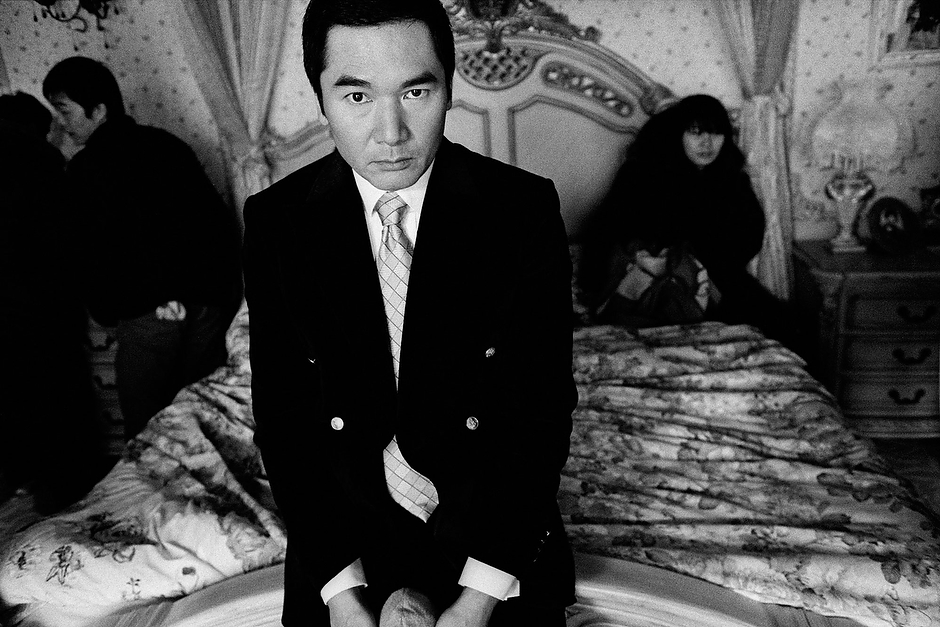 Hong Kong actor Alex Fong rests with set workers during production of <em>The Last Night of Madam Chin</em> in the Shanghai suburb of Chedun.