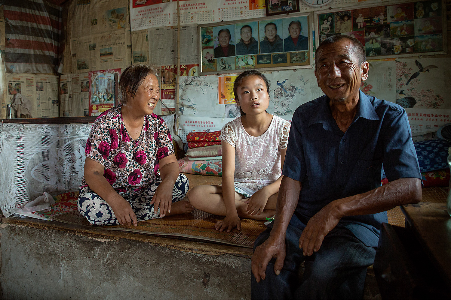Swallow, 14, sits with her caretakers, her grandfather and his partner, in their home. Her father died in an accident when she was younger and her motherlives and works in Yuncheng, the closest biggest city, but never visits or contacts her. Swallow says her dream is to visit family in Yuncheng, less than 31 miles away. Swallow benefits from the support of one of China's growing number of 'Barefoot Social Workers'—community-selected individuals who are trained by UNICEF to provide child protection and welfare services in rural villages. Photo by Sharron Lovell @sharron_l / UNICEF China