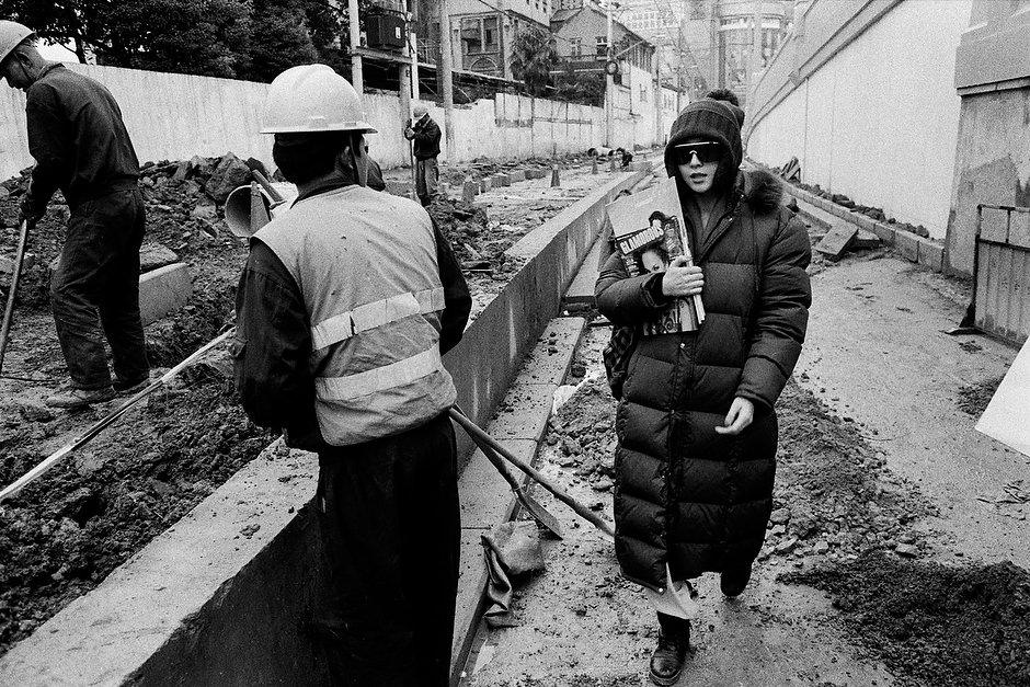 Bingbing, laden with American fashion magazines and sporting her usual disguise of dark glasses and a low hat, strolls confidently through a construction site while under the watchful gaze of laborers and a distant paparazzo before arriving at a location shoot in a prewar theater near the Qipu Lu shopping district in central Shanghai.
