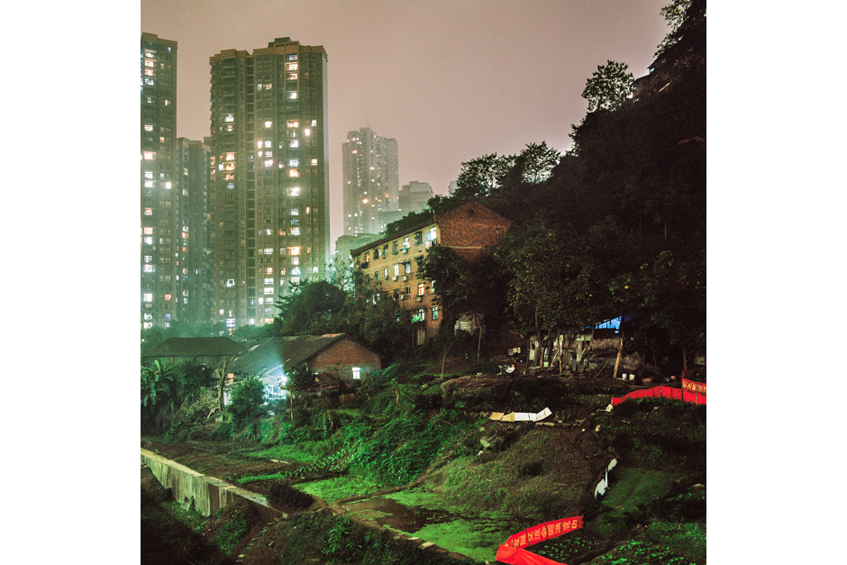 In the Shapingba district, a house and surrounding gardens are lit by urban light pollution as skyscrapers loom large from a nearby housing development project that are gaining most of the lands in this part of town.