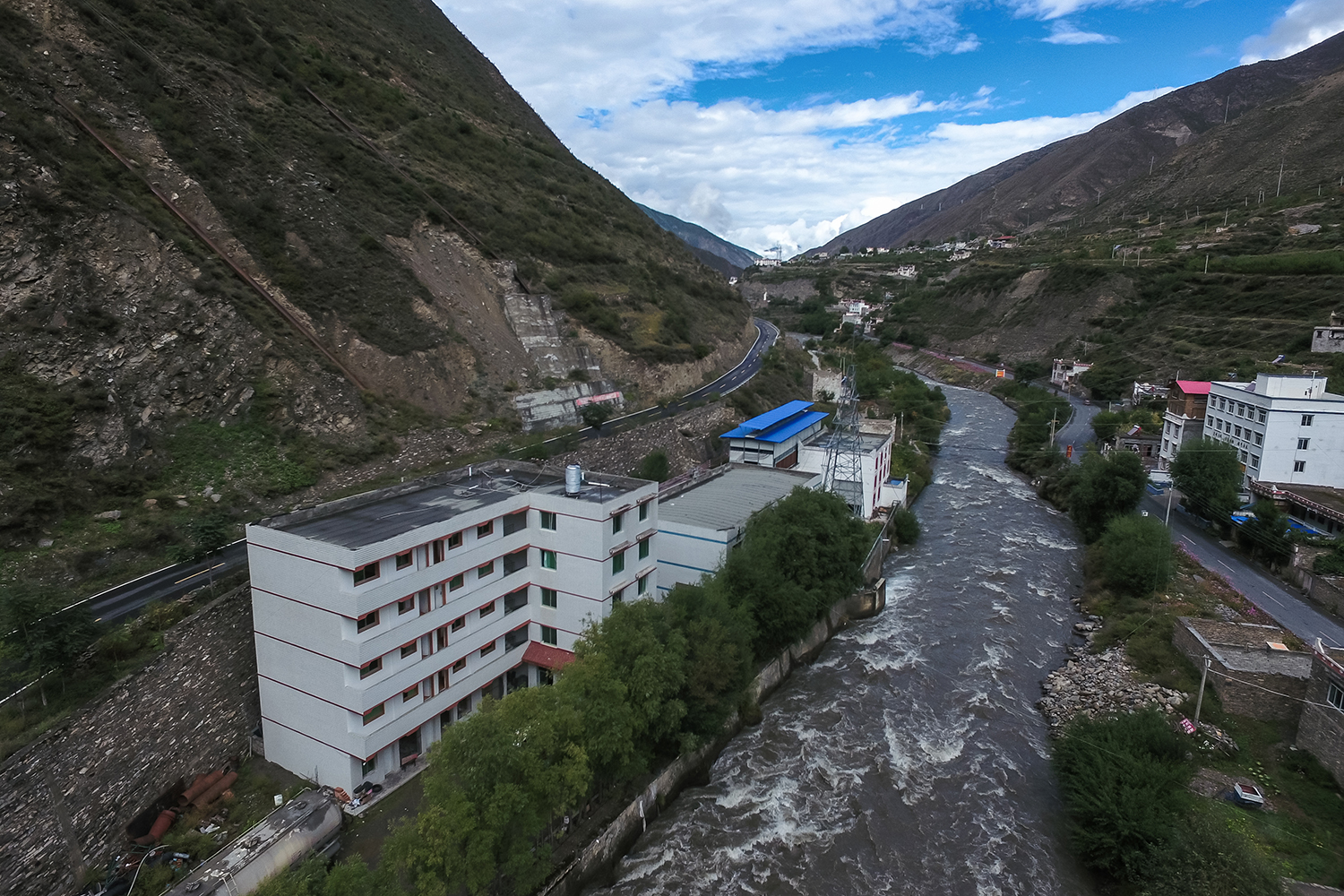 "A Bitcoin ""mine"" with a blue tin roof sits next to a hydroelectric power plant in Ngawa (Aba) Tibetan and Qiang Autonomous Prefecture, Sichuan province, September 27, 2016. Located at the eastern edge of the Tibetan Plateau, the area has abundant hydropower, a key factor in making energy intensive mines cost effective. Electricity typically accounts for 60-70 percent of a bitcoin mine's expenses."
