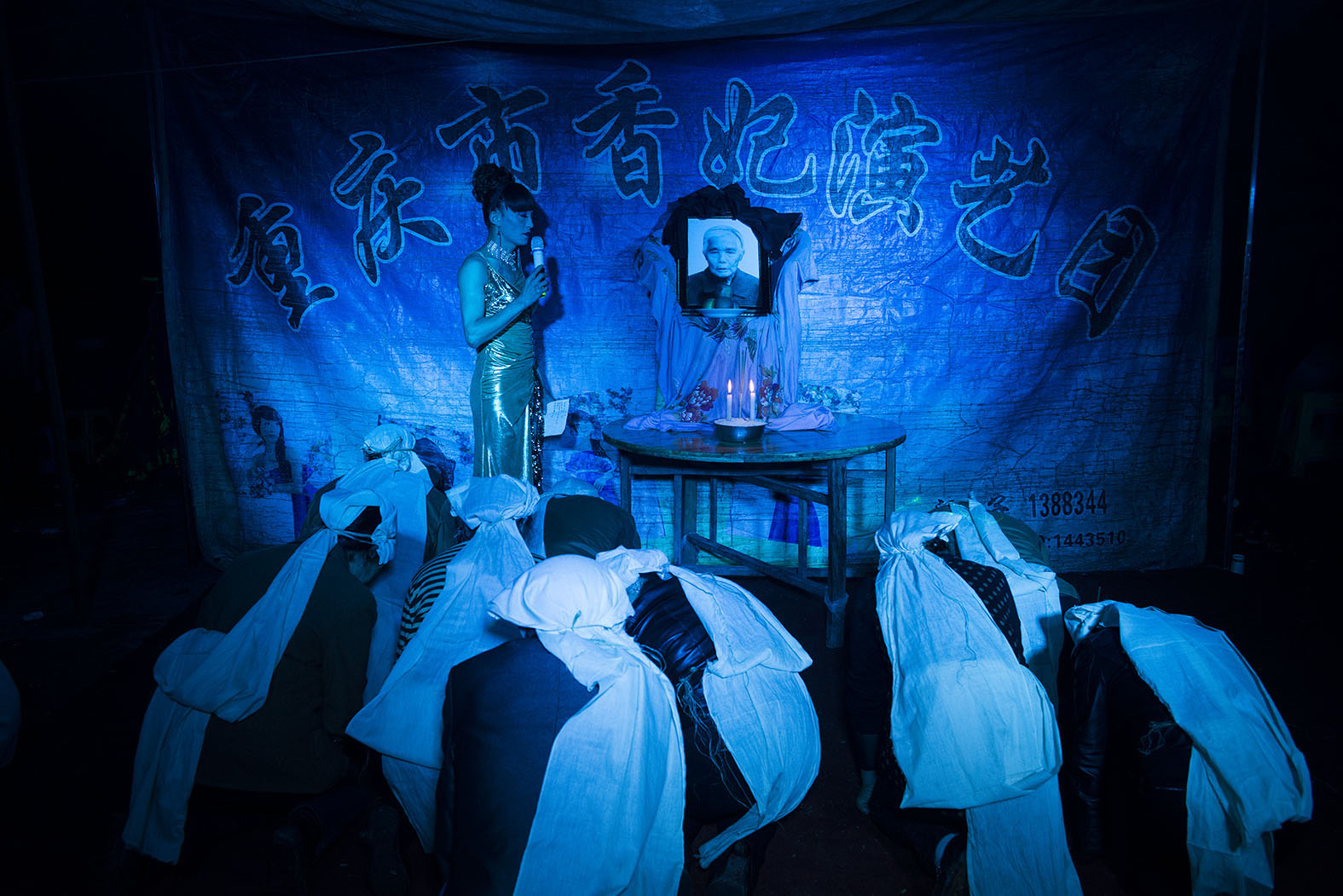 Family members kneel in front of a portrait of the departed as Liangzi hosts a funeral ceremony, April 10, 2014. As a funeral performer, Liangzi is skilled at singing, dancing, and wailing. She is proud of her wailing skill, and she tries to cry naturally at every funeral.