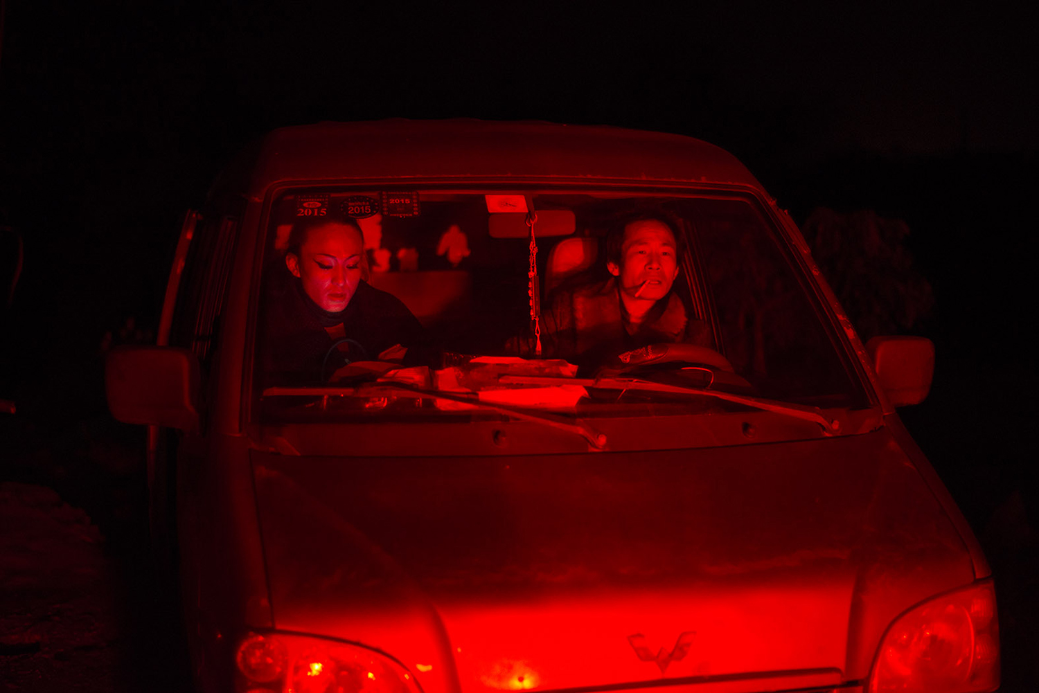 Liangzi counts money in a car after a funeral performance, February 24, 2015.