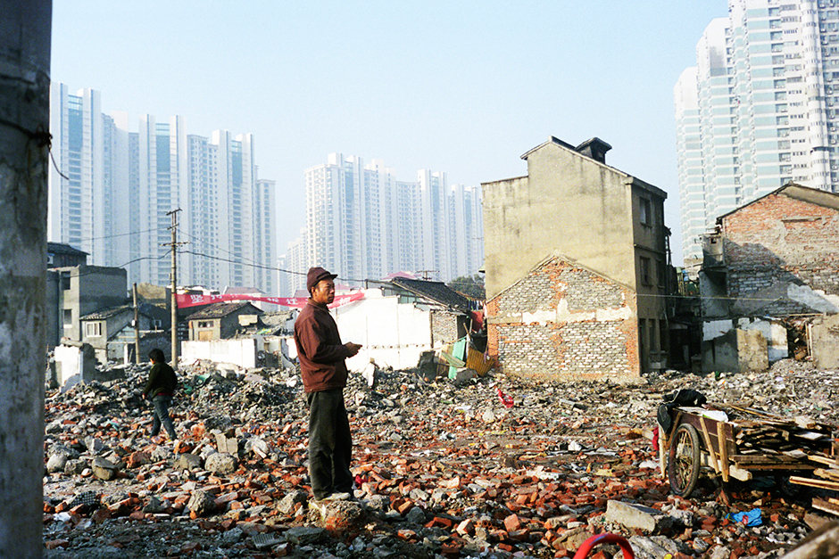 A man stands on rubble in Putuo District, Shanghai, November 2009. This neighborhood would soon be demolished to make way for a new residential development.