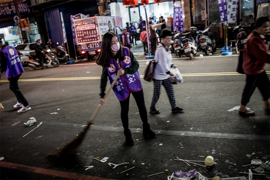 A DPP campaign worker sweeps the street after a rally for Legislative Yuan candidate Zheng Yong-jin and presidential candidate Tsai Ying-wen in Zhudong, Hsinchu County.