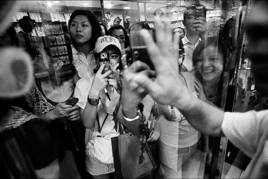 Eager fans and mall employees—startled from their daily routines by the presence of Bingbing and her entourage—crowd the windows outside a jewelry store where the starlet is shopping in Guangzhou.