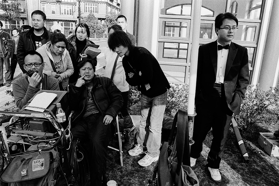Directors and a crowd of associate producers review footage on location while filming <em>The Last Night of Madam Chin</em> in Shanghai's Songjiang suburb.
