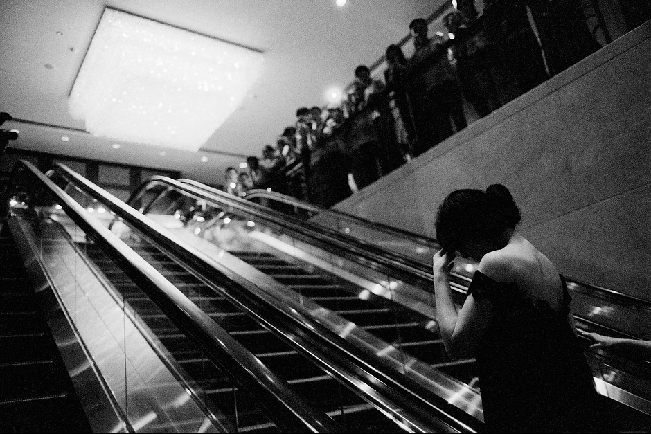 The starlet grabs a fleeting moment of repose while riding an escalator to a waiting crowd of fans and press at a promotional event in Shenzhen.