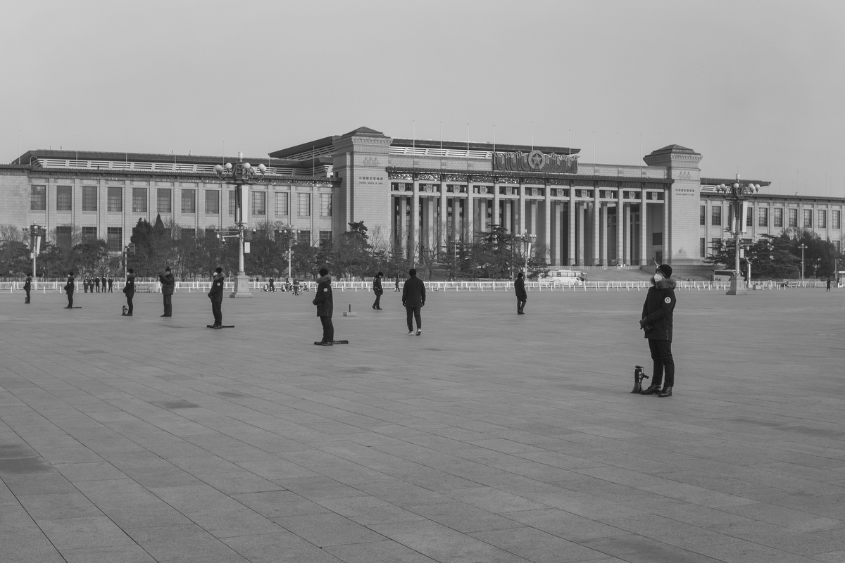 People's Armed Police officers, dressed in black, stand across Tiananmen Square, February 3, 2020.