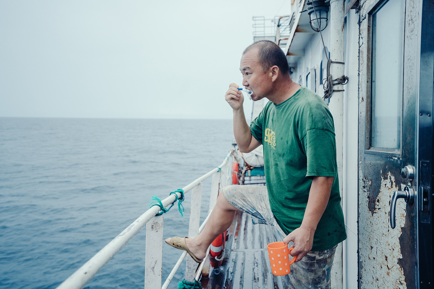 Jin, the 44-year-old Second Engineer, brushes his teeth on deck, July 22, 2016. Jin, who first came to work in Africa in 2008, is from Henan province. Captain Xu's ship left port in Dakar, Senegal on July 20, 2016. Industrial fishing vessels like this one typically spend 20-30 days on the water at a stretch.
