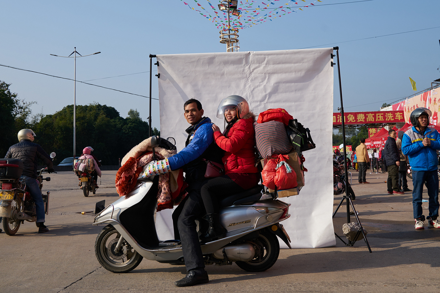 January 22, six days before the Lunar New Year, a migrant couple rides a motorcycle from Zhongshan, Guangdong province to Pingnan in Guangxi, to go home for the holiday. The trip is 245 miles. Although biking is far from the safest travel option, it's cheap and a good way to avoid overcrowded trains and buses. (Liang Yingfei/Caixin)