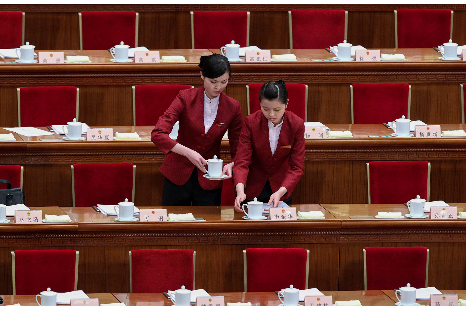 Two waitresses arrange tea cups at each parliament member's seat in the Great Hall of the People, March 5, 2010, for the Third Session of the 11th National People's Congress.