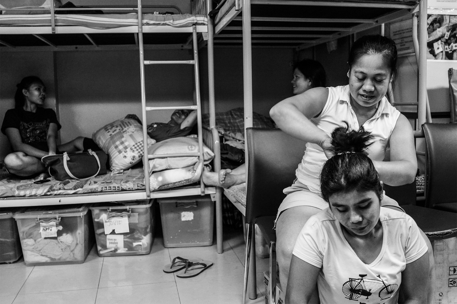 Judy, a caretaker in Bethune House, helps Aniya, an Indonesian domestic worker, fix her hair in the sleeping/common area in the shelter. Aniya says she ran away from her employer after working without pay for more than a year. She says her employer brought her to mainland China to work under terrible living conditions for more than a year. Because she was hired under Hong Kong labor laws, bringing her to the mainland to work was illegal. Aniya cannot read or speak English or Cantonese, and she did not pursue a case against her employer. She says she just wants to go home to Indonesia.