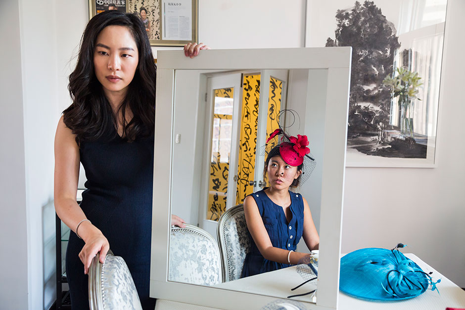 Sara Jane Ho, 29, founder of Institute Sarita, a high-end etiquette school in Beijing, a Hong Kong native who was educated at Phillips Exeter Academy, Georgetown University, Harvard Business School, and Institute Villa Pierrefeu, teaches first-time student Jessie Wen how to wear a hat.