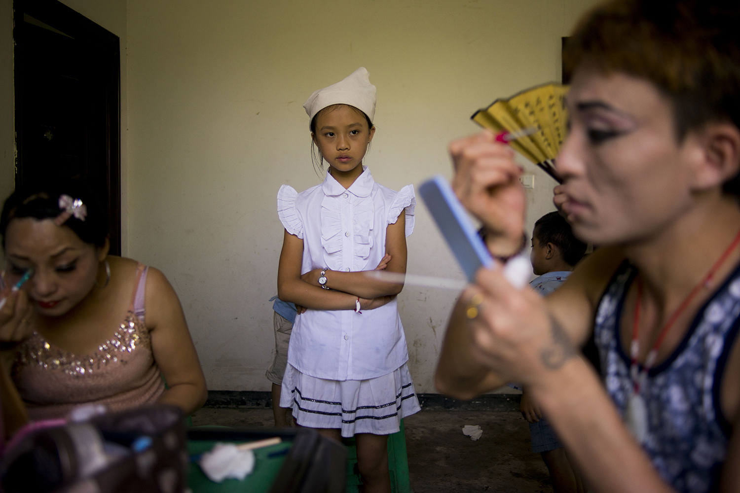 A girl watches Liangzi putting on makeup before a funeral performance, Dazu district of Chongqing municipality, July 24, 2016.