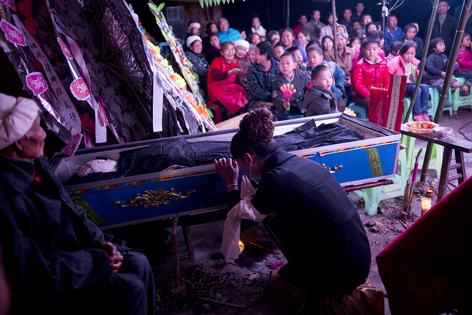 Liangzi kneels beside a dead body in front of funeral attendees, November 9, 2014.