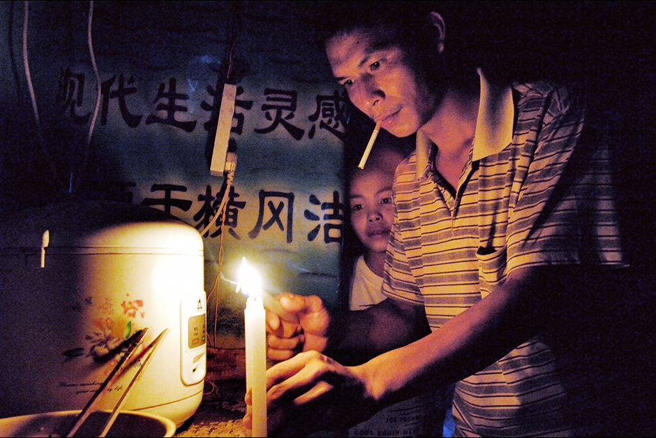 Wuwucun factory worker Xu Huali's husband, Zhao Xiaoyun, lights candles during one of the rolling blackouts that were common at the time this photograph was made in 2005.