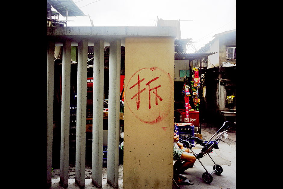 "The Chinese character <em>chai</em>, meaning ""to demolish,"" marks the wall at the entrance to the neighborhood of Lane 1289 West Yan'an Road, Shanghai, July 31, 2009. The government usually marks buildings and neighborhoods slated for demolition with this character; in this case, however, it was the residents who painted it, with the hope that an urban renewal project would finally reach them and they would receive money to move out. Officials from the Neighborhood Committee (<em>jiedao banshi chu</em>) routinely erased the marking, only to see it repainted by the residents soon after."