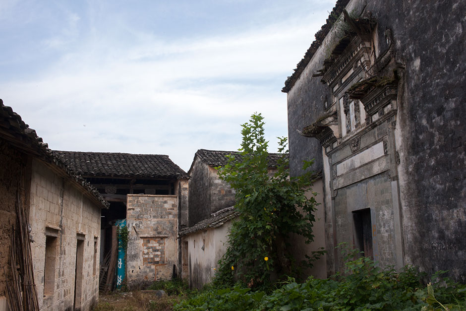 Despite its poor condition, Mingxian Hall, the exterior wall, seen at the right, is a fine example of the distinctive architecture of the Huizhou region. The hall was built during the eighteenth century. The original stone carvings, murals, stele, and the couplets that adorned its gates were stripped from the facade after it was confiscated by the government when the Communists came to power in 1949.
