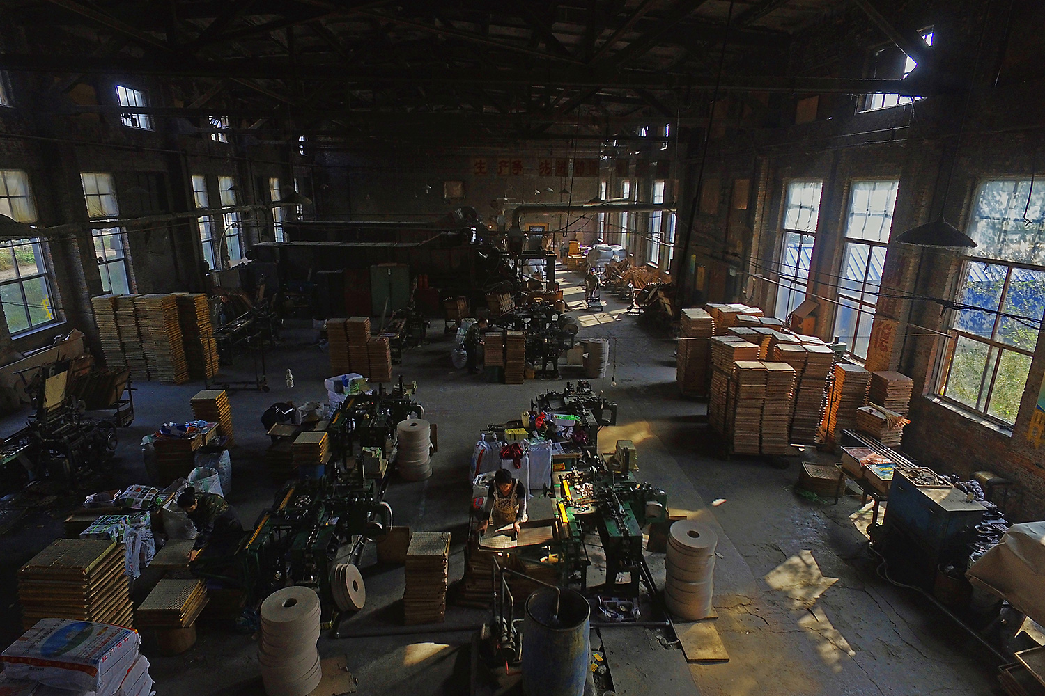Old workshop equipment and slogans from the 1970s are still on the walls of the Yanbian factory. Workers follow long-used methods amid the thundering of machines. Here, pieces of wood are turned into thin matchsticks, and as they pass through the noisy machines, each is topped with a 'little red cap.' A group of workers operates the controls, and packs the finished matches into boxes.