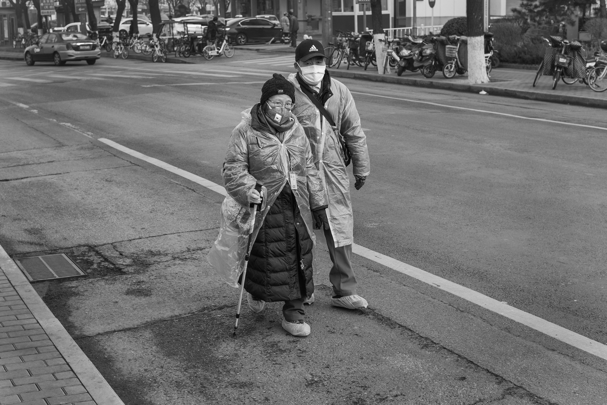 A woman and man walk down Tianqiao Yong'an Road with plastic ponchos and shoe covers, February 11, 2020.